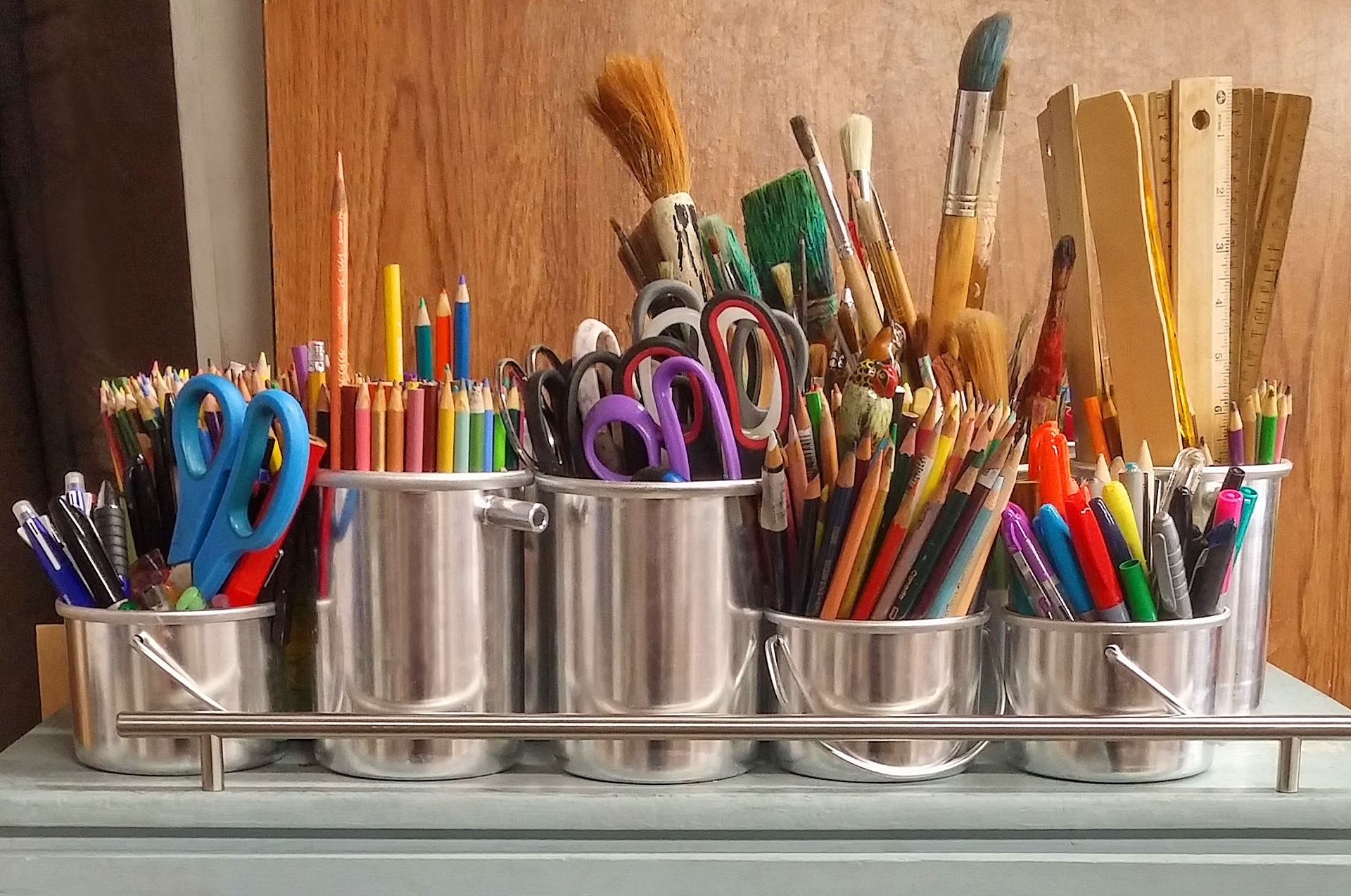 Silver buckets with pencils, markers, paint brushes, and other art supplies